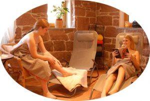 Wellnessbereich vor der Sauna mit 2 Liegestühlen auf denen Frauen liegen und ein Buch lesen.