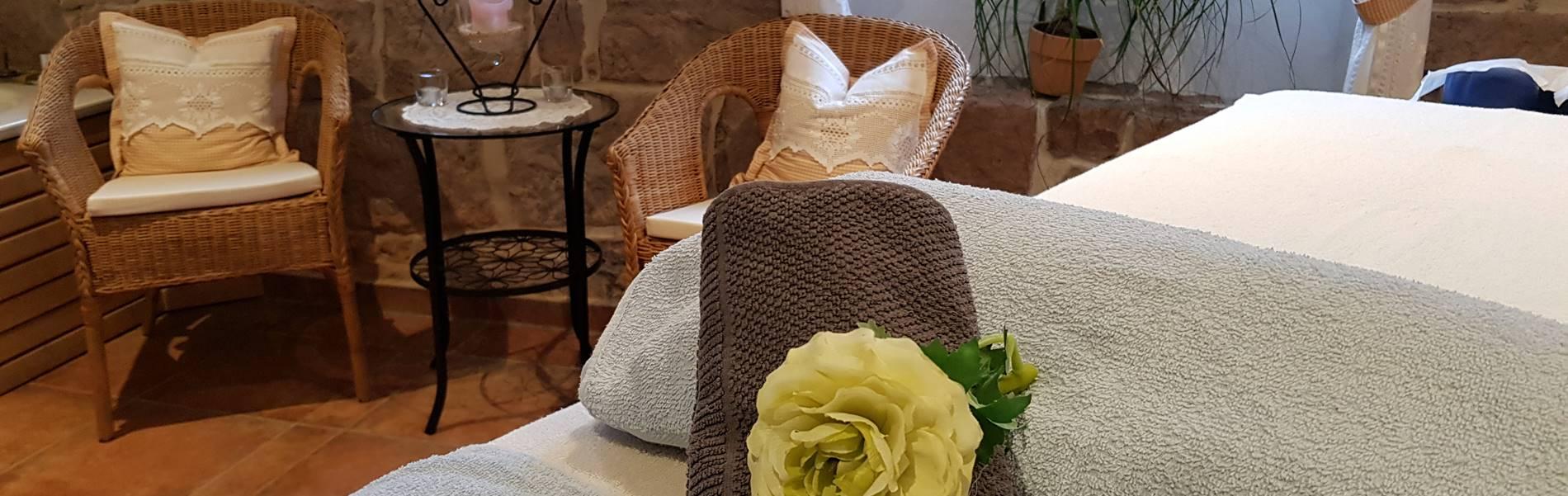 Massageliege mit Handtuch und Rosendeko